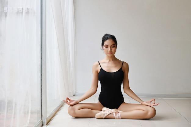 La bella donna asiatica in buona salute in vestito da balletto che gode nel medita con yoga posa a casa con rilassamento