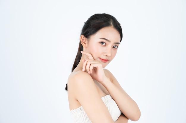 La bella donna asiatica in maglietta bianca mostra la pelle luminosa e sana.