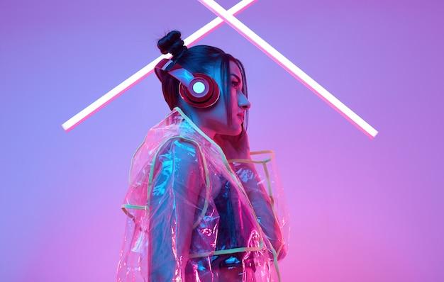 La bella donna asiatica in un impermeabile ascolta musica in cuffie intorno al neon variopinto
