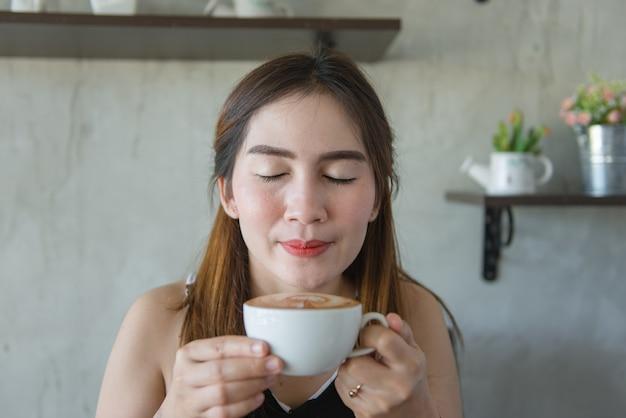 La bella donna asiatica odora il caffè caldo fresco in una caffetteria