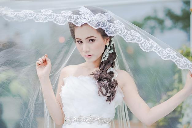 La bella donna asiatica porta un vestito da sposa