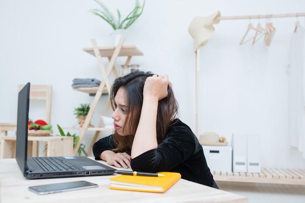 La bella donna asiatica sorridente dello studente che impara dal servizio di istruzione online, giovane donna asiatica che guarda il computer portatile del computer confonde circa il suo lavoro di affari