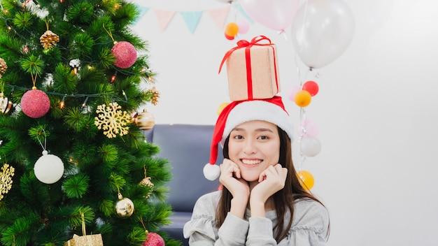 La bella donna asiatica sta decorando l'albero di natale nella stanza bianca con il contenitore di regalo disposto sulla testa. fronte sorridente e felice di celebrare la festa del capodanno del festivel.
