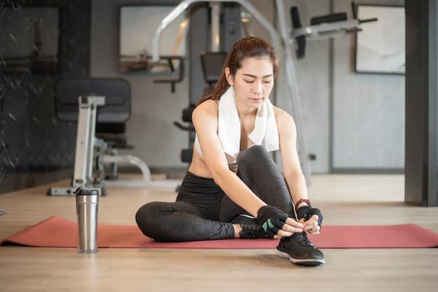 La bella donna asiatica sta facendo l'esercizio in palestra