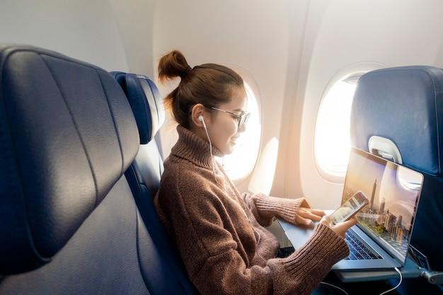 La bella donna asiatica sta lavorando con il computer portatile in aeroplano