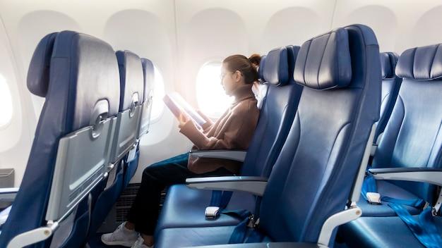 La bella donna asiatica sta leggendo la rivista in aeroplano
