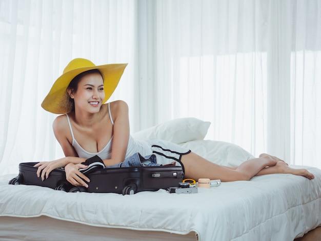 La bella donna asiatica sta preparando le borse per andare in vacanza
