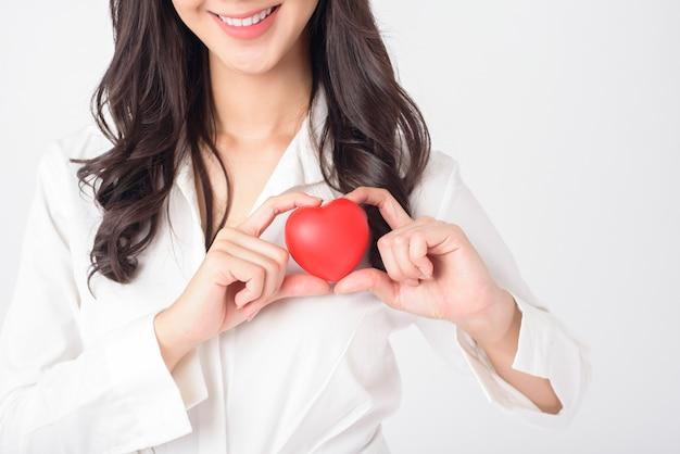 La bella donna asiatica sta tenendo il cuore rosso (concetto di sanità)