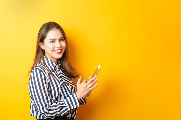 La bella donna asiatica sta usando la sua compressa su fondo giallo