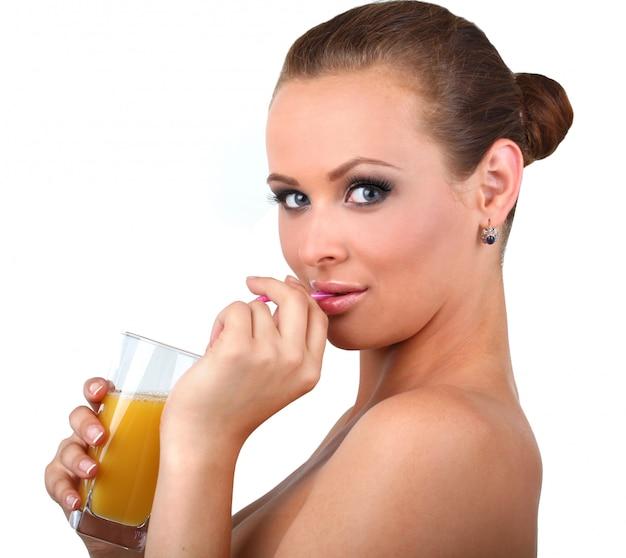 La bella donna beve il succo di arancia fresco