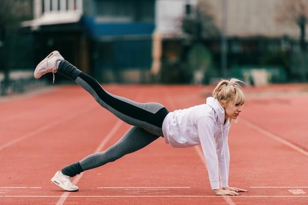 La bella donna bionda caucasica che fa la gamba della plancia si alza sulla pista prima di correre. figura intera, vista laterale.