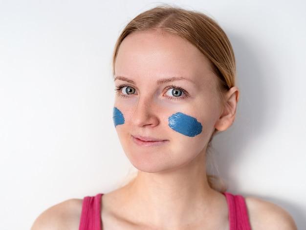 La bella donna bionda che ha la maschera facciale dell'argilla blu si applica dall'estetista. la donna con una maschera sulle guance sta sorridendo