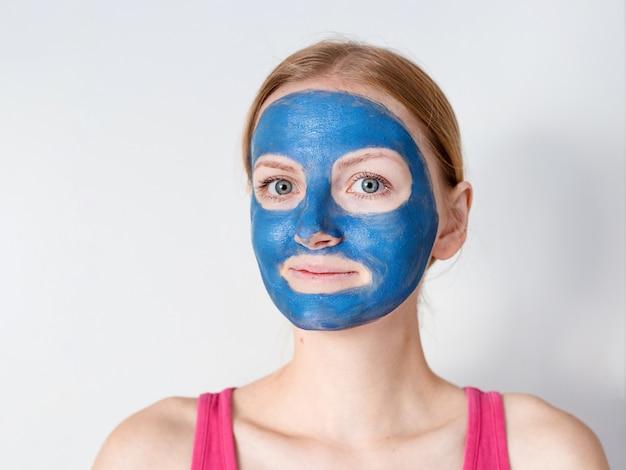 La bella donna bionda che ha la maschera facciale dell'argilla blu si applica dall'estetista.