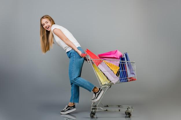 La bella donna bionda felice ha carretto a mano con i sacchetti della spesa variopinti isolati sopra grey
