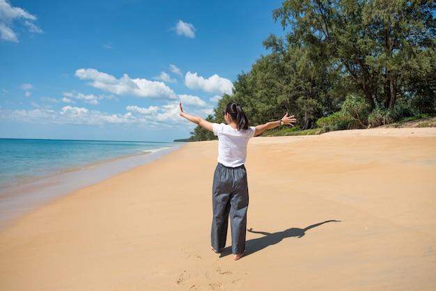 La bella donna cammina sulla spiaggia
