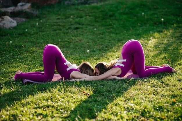 La bella donna castana che indossa l'usura attillata attiva che esegue l'yoga posa in un parco sulle stuoie porpora con i chiarori sole molli che vengono attraverso gli alberi