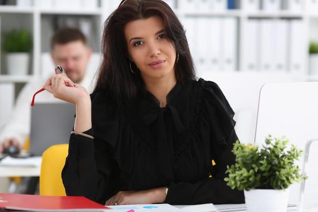 La bella donna castana sorridente si siede alla tavola di lavoro