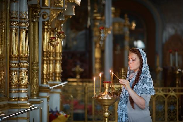 La bella donna caucasica russa con i capelli rossi e una sciarpa in testa è nella chiesa ortodossa, accende una candela e prega davanti all'icona.