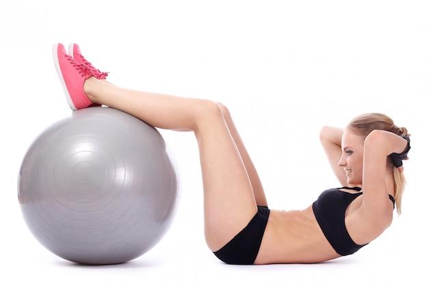 La bella donna che fa gli addominali si esercita con la palla di forma fisica
