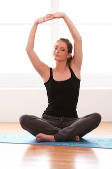 La bella donna che fa l'yoga si esercita a casa