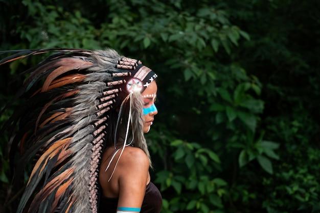 La bella donna che indossa il copricapo di piume di uccelli, dipinto di colore blu sul viso, ritratto della modella in posa nella foresta, luce sfocata intorno