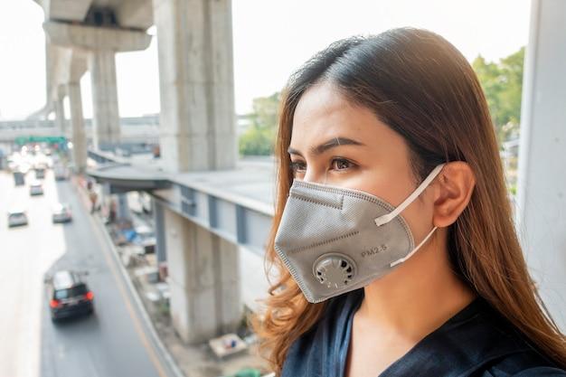 La bella donna che indossa l'anti maschera antipolvere protegge l'inquinamento atmosferico e pm 2.5 sulla città della via