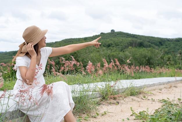 La bella donna che indossa un abito bianco seduto sul pavimento di cemento, punta il dito verso l'alto in aria, con sorriso e faccia felice, tempo di relax, vista sulla campagna