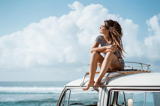 La bella donna che si rilassa gode della natura di viaggio stradale che si siede sulla r