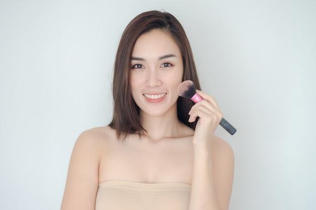 La bella donna con la spazzola cosmetica della polvere per compone. la ragazza asiatica sveglia mostra la sua pelle perfetta
