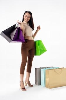 La bella donna con le borse della spesa in mano, con sorriso e felice sensazione