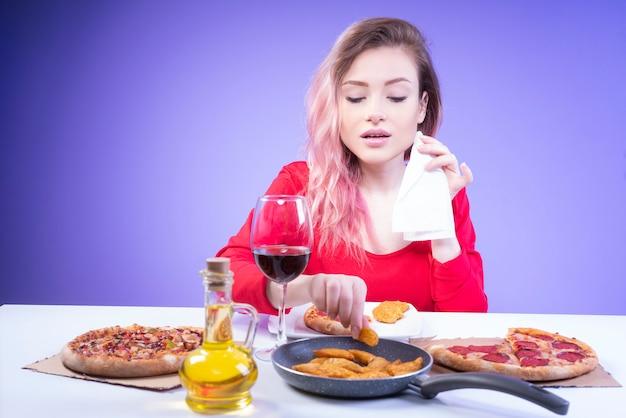 La bella donna con un tovagliolo in una mano prende un cuneo di patata fritta
