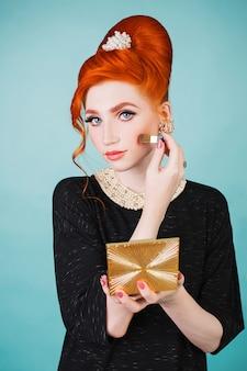 La bella donna dai capelli rossi con la retro acconciatura e trucco sta tenendo uno specchio in sua mano su un fondo blu. modello con i capelli rossi con un pennello per il trucco in mano
