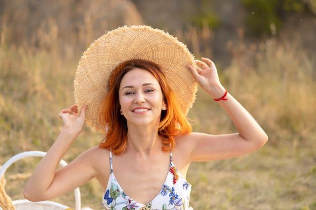 La bella donna dai capelli rossi gode del tramonto sulla natura. pic-nic in campo.