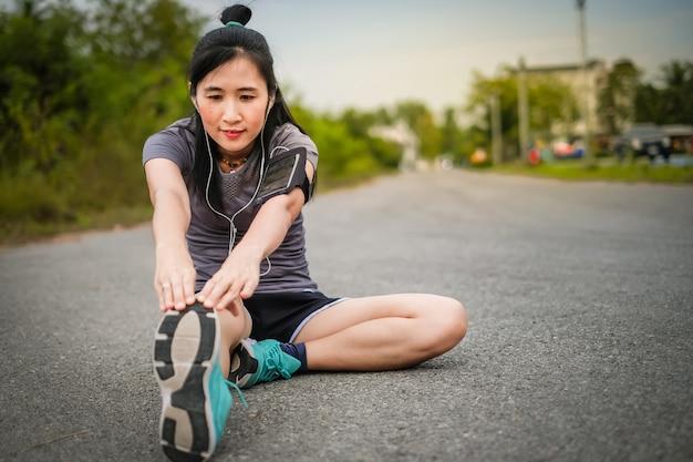 La bella donna dell'asia negli articoli di sport riscalda prima di correre sulla strada.