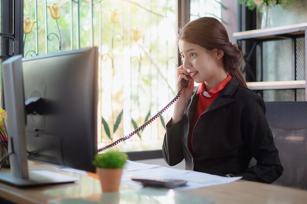La bella donna di affari discute con il partner dal telefono in ufficio.