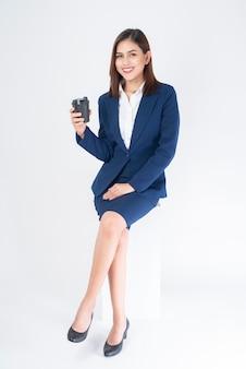 La bella donna di affari in vestito blu sta bevendo il caffè