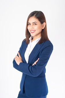 La bella donna di affari in vestito blu sta sorridendo su fondo bianco