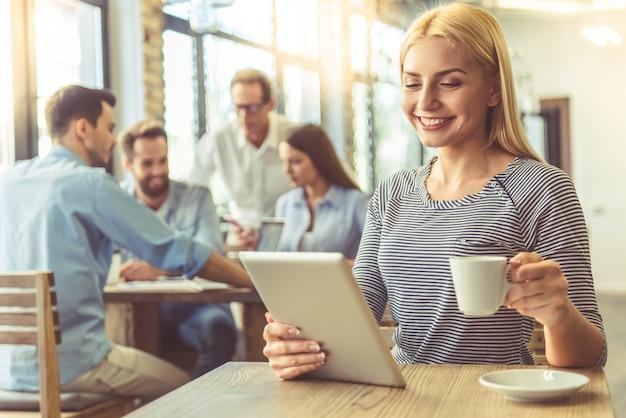 La bella donna di affari sta bevendo il caffè e sorridere.