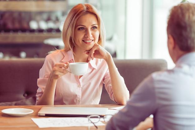 La bella donna di affari sta bevendo il caffè.