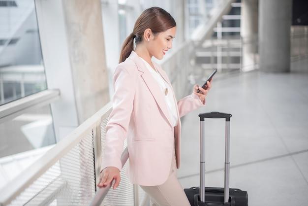 La bella donna di affari sta camminando in aeroporto, concetto di viaggio d'affari