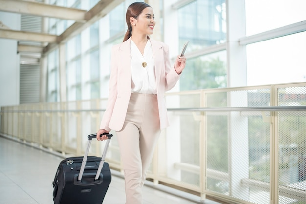 La bella donna di affari sta camminando in aeroporto