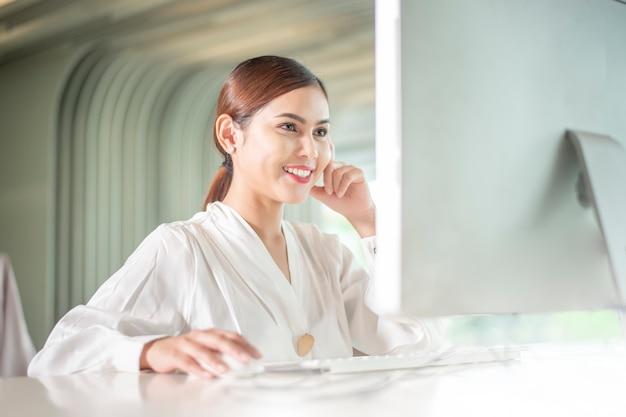 La bella donna di affari sta lavorando con il suo calcolatore