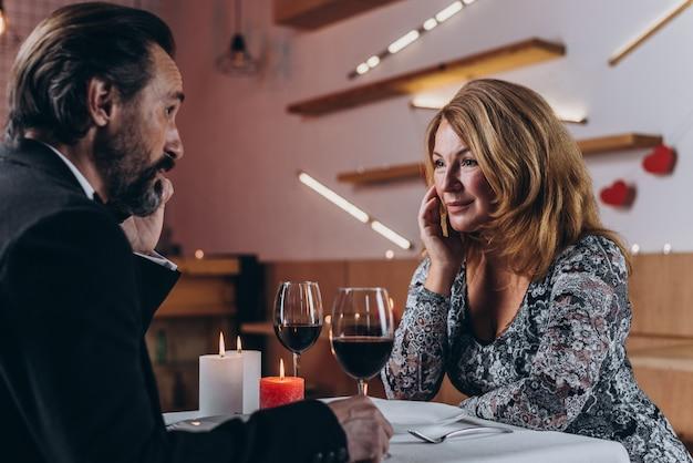 La bella donna di mezza età esamina un uomo con uno sguardo amoroso.