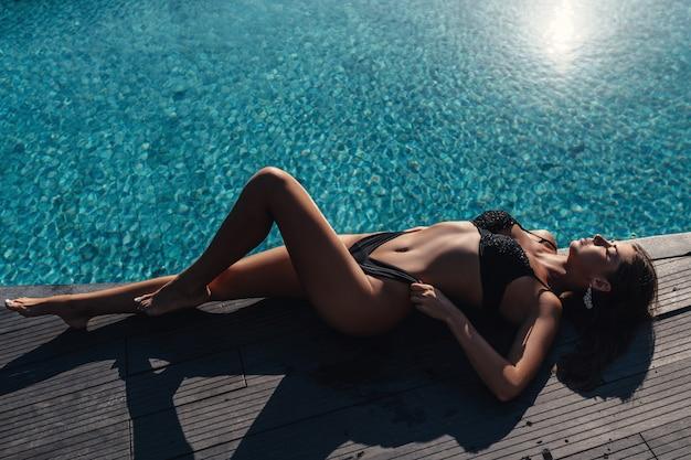 La bella donna di modello in un bikini nero si rilassa vicino allo stagno. abbigliamento estivo moda spiaggia. copia spazio