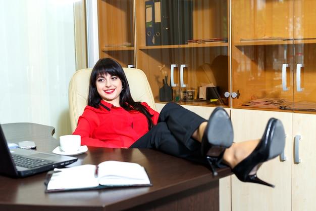La bella donna di sorriso si distende in un ufficio
