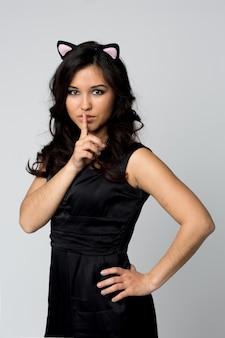 La bella donna di trucco che mostra il silenzio firma il dito vicino alle labbra su luce isolata