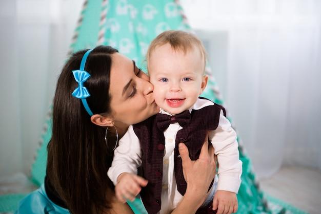 La bella donna e suo figlio piccolo stanno giocando e sorridendo, su fondo blu.
