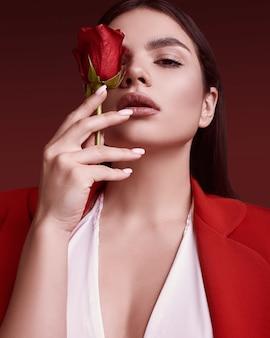 La bella donna elegante in un vestito alla moda rosso con è aumentato