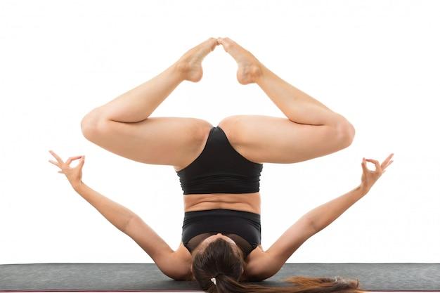 La bella donna flessibile che fa l'yoga posa su fondo bianco