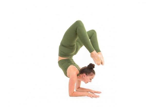 La bella donna flessibile che fa l'yoga posa sulla superficie bianca
